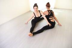 做两名体操运动员的妇女舒展在白色内部的锻炼 库存图片