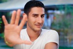年轻做中止姿态的人上升的手 免版税库存图片
