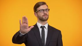 做中止姿态的企业人,拒绝劳累过度,橙色背景 影视素材