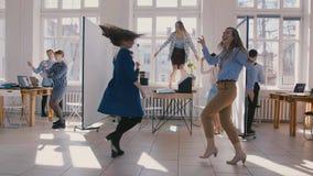 做乐趣优胜者舞蹈的两个愉快的女性商业公司伙伴庆祝与同事慢动作一起 股票视频