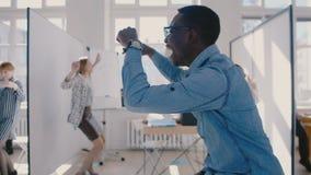 做乐趣疯狂的庆祝舞蹈,与同事慢动作的份额成功的激动的愉快的非裔美国人的商人 股票录像