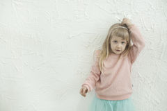 做乐趣面孔的小公主女孩在白色砖墙backgtound 免版税库存照片