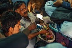 做乘客的印度- 12月2012未认出的人食物在印地安铁路普通车里面在2012年12月寸 免版税库存照片