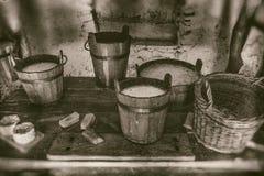 做乳酪和日志产品、桶牛奶,奶油和酸乳老方式在木桌 免版税库存照片
