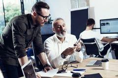 做了不起的时间的小组两个工友在工作过程中刹车在现代办公室 使用机动性的成人有胡子的人 免版税图库摄影
