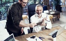 做了不起的时间的小组两个工友在工作过程中刹车在现代办公室 成人有胡子的人观看的机动性 免版税库存图片