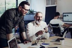 做了不起的时间的小组两个工友在运作的过程中刹车在现代办公室 成人有胡子的人观看的录影 免版税图库摄影