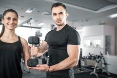 做二头肌的妇女在与她的个人教练员的健身房卷曲 免版税图库摄影