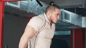 做二头肌的年轻大力士在健身房行使 免版税库存照片