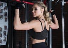 做二头肌锻炼的健身妇女 免版税库存图片