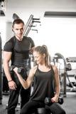做二头肌的妇女在与她的个人教练员的健身房卷曲 免版税库存照片