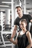 做二头肌的妇女在与她的个人教练员的健身房卷曲 免版税库存图片