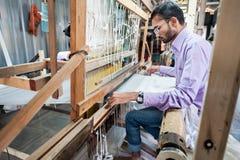做五颜六色的绢丝织品的人们由印地安编织机 免版税库存图片