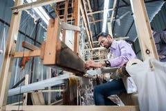 做五颜六色的绢丝织品的人们由印地安编织机 库存照片