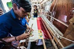 做五颜六色的绢丝织品的人们由印地安编织机 免版税库存照片