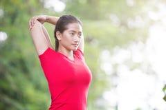 做亚裔的妇女舒展锻炼在室外发怒火车期间 免版税库存照片