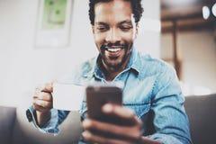 做交谈的微笑的有胡子的非洲人特写镜头在智能手机在现代家 使用机动性的概念人 免版税库存照片