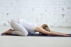 做产前儿童瑜伽姿势, Balasana的怀孕的少妇 免版税库存照片
