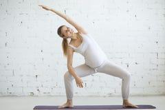 做产前瑜伽的怀孕的少妇 与边的女神姿势 免版税图库摄影