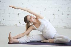 做产前瑜伽的怀孕的少妇 在Janu先生的旁边弯 免版税库存图片