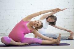 做产前瑜伽的怀孕的少妇 坚硬对膝盖批转B 库存图片