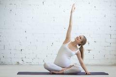 做产前瑜伽的怀孕的少妇 旁边舒展 免版税库存照片