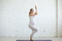 做产前瑜伽的怀孕的少妇 老鹰姿势 免版税库存图片