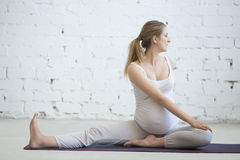 做产前瑜伽的怀孕的少妇 脊髓转弯在Janu S 免版税库存图片