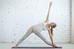 做产前瑜伽的怀孕的少妇 延长的三角姿势 库存照片
