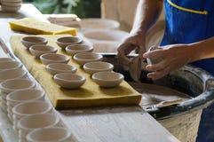 做人的陶瓷工在给上釉的液体,泰国投入了白色碗 库存图片