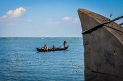 做他们的工作的渔夫,观看从居住船 免版税图库摄影