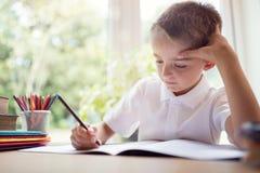 做他的学校工作或家庭作业的男孩 免版税库存照片