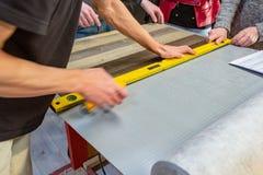 做他的工作的木匠在木匠业车间 木匠业车间测量和裁减层压制品的一个人 免版税图库摄影
