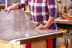 做他的工作的木匠在木匠业车间 木匠业车间测量和裁减层压制品的一个人 免版税库存图片