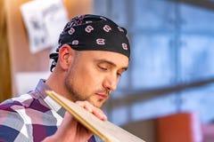做他的工作的木匠在木匠业车间 木匠业车间测量和裁减层压制品的一个人 图库摄影
