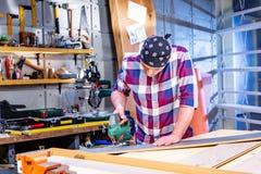 做他的工作的木匠在木匠业车间 木匠业车间测量和裁减层压制品的一个人 库存照片
