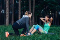 做仰卧起坐的微笑的亭亭玉立的女孩,当协助她的女性朋友持续脚时 两个女朋友训练 图库摄影