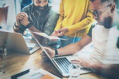 做伟大的激发灵感的小组三个工友在工作过程中在现代办公室 年轻有胡子人观看 库存照片