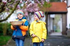 做传统复活节彩蛋的两个小孩男孩和朋友寻找 库存图片