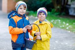 做传统复活节彩蛋的两个小孩男孩和朋友寻找 免版税库存照片