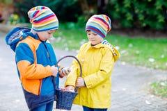 做传统复活节彩蛋的两个小孩男孩和朋友寻找 图库摄影