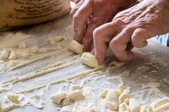 做传统新鲜的面团的意大利妇女的手在一张大理石桌 图库摄影