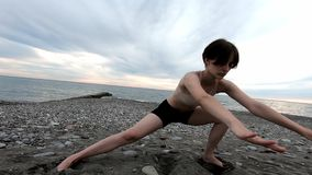做伸展运动的年轻美女在海滨 r E 股票录像