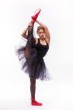做体操分裂的黑芭蕾舞短裙礼服的白肤金发的美丽的女孩 免版税库存图片