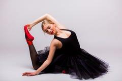 做体操分裂的黑芭蕾舞短裙礼服的白肤金发的美丽的女孩 库存图片