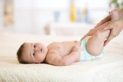 做体操婴孩的妈妈或massagist 免版税库存图片