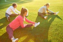 做体操的三个年轻体育女孩在绿草的早晨 露天,黎明,健身,健康,体育 免版税库存照片
