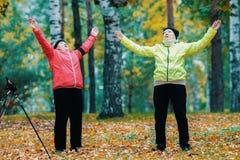 做体操的成熟妇女在秋天公园在斯堪的纳维亚步行以后 库存图片