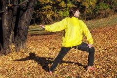 做体操的年长俏丽的妇女在秋天森林里 免版税库存照片