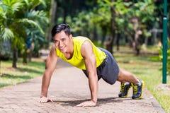 做体育俯卧撑的坚强的亚裔人在公园 库存照片